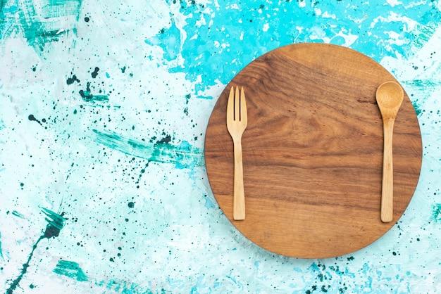 上面図木製カトラリーフォークと水色の背景のスプーン木製の明るい色