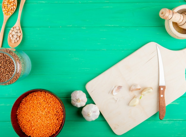 Vista superiore del tagliere di legno con coltello e aglio e lenticchie rosse crude in una ciotola su fondo verde con lo spazio della copia