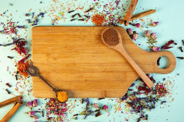 Top view of a wooden cutting board with a spoon of cinnamon powder on blue