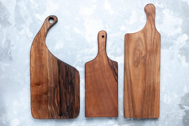 明るい背景の木製の写真の色の食品用の木材から作られた異なる成形された上面図の木製の机