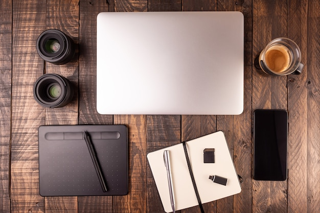 Top view of wooden desktop with laptop, table, coffee, notebook, mobile, memory cards.