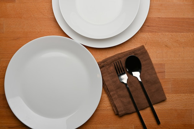 Top view of wooden dinning table with mock up ceramic plates cutlery and napkin