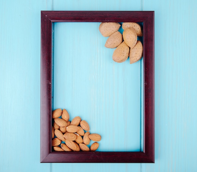 Top view of wooden empty picture frame with almond on blue wooden background