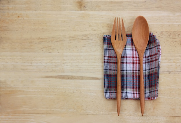 Top view wooden fork and spoon on abstract fabric on table with copy space.