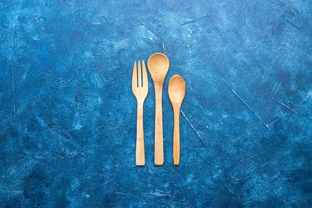 Top view wooden fork spoon knife on blue table with free place