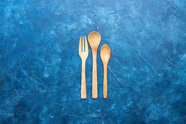 Coltello cucchiaio forchetta in legno vista dall'alto sul tavolo blu con posto libero