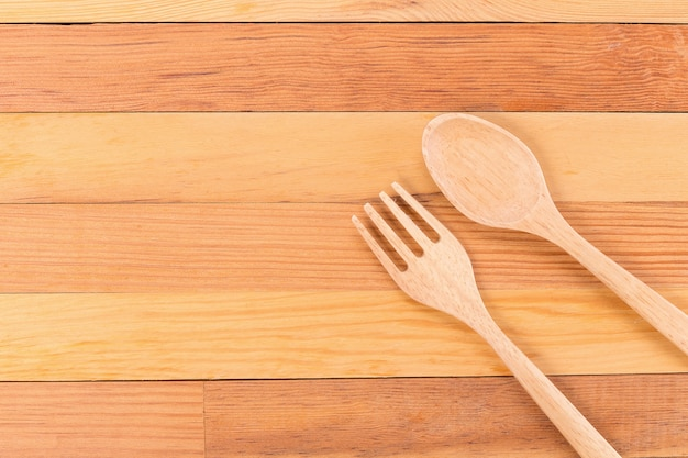 Top view of wooden fork and spoon on light wooden background