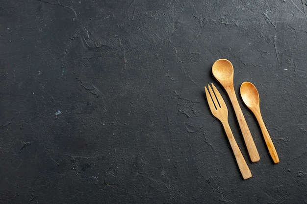 Top view wooden fork and spoons on dark table with free space