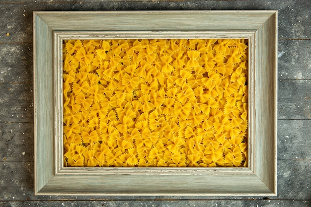 Top view of a wooden frame filled with raw pasta farfalle