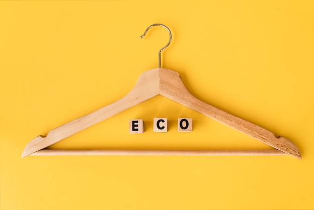 Top view wooden hanger with yellow background