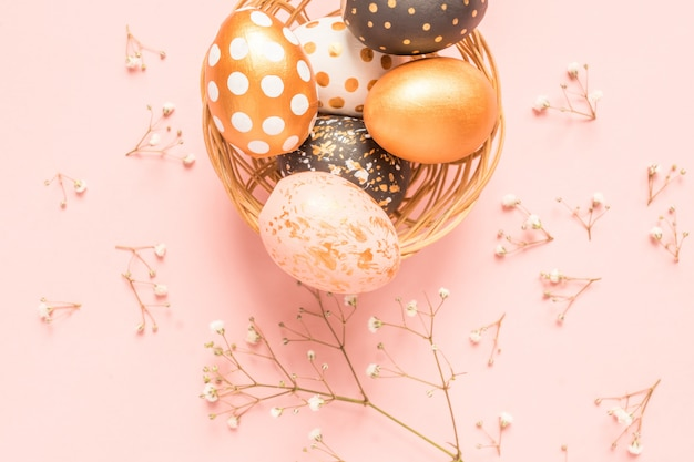 Top view of wooden painted eggs in gold, black and rose colors in wicker basket with branch of gypsophila on pink background. happy easter background