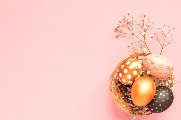 Top view of wooden painted eggs in gold, black and rose colors in wicker basket with branch of gypsophila on pink background.