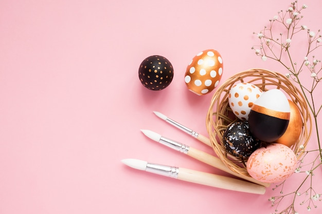 Top view of wooden painted eggs in gold, black and rose colors with branch of gypsophila and paint brushes on pink background.