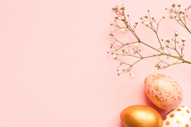 Top view of wooden painted eggs in gold, black and rose colors with branch of gypsophila on pink background. happy easter background with copy space