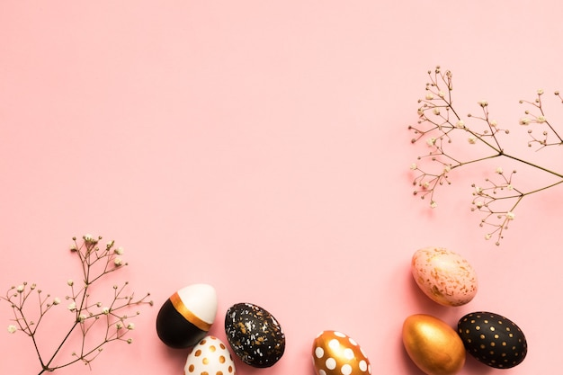 Top view of wooden painted eggs in gold, black and rose colors with branch of gypsophila on pink background. happy easter background with copy spaceñŽ