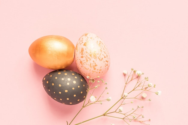 Top view of wooden painted eggs in gold, black and rose colors with branch of gypsophila on pink background. happy easter background