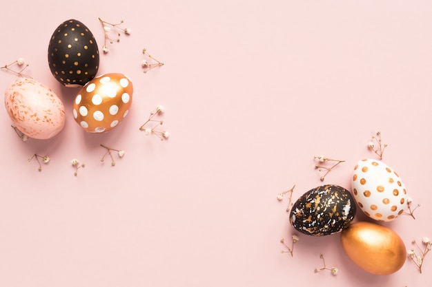 Top view of wooden painted eggs in gold, black and rose colors with branch of gypsophila on pink background.