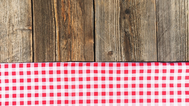 Top view of wooden plank and checkered tablecloth