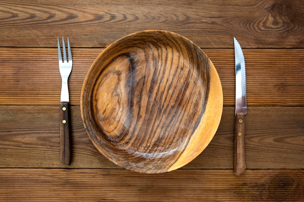 Top view of wooden roud plate with fork and knife, on wooden table. copy space, menu, recipe or dieting concept.