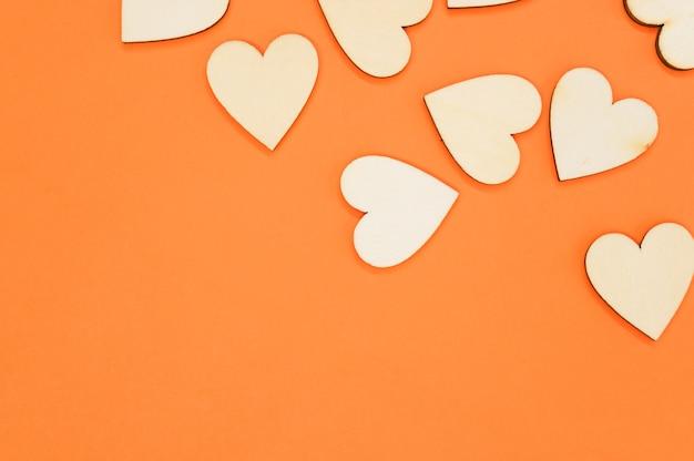 Vista dall'alto dei cuori a forma di legno sulla superficie arancione - spazio per il testo