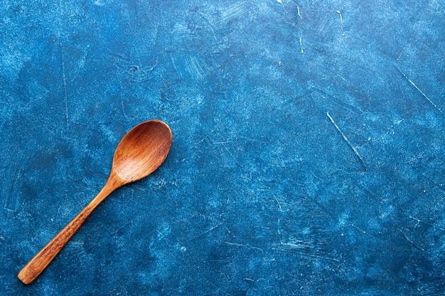 Cucchiaio di legno vista dall'alto su fondo blu con spazio di copia