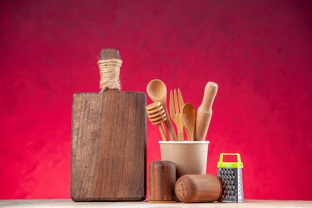 Top view of wooden spoon in an empty plastic coffee pot cutting board grater on pink surface