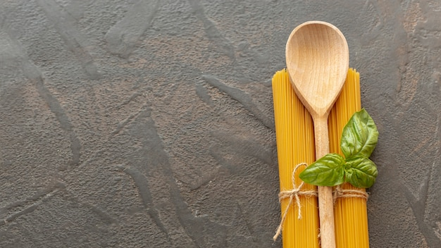 Top view of wooden spoon and spaghetti with copy space