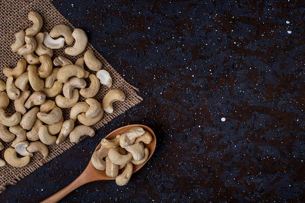 Top view of a wooden spoon with cashew on black background with copy space