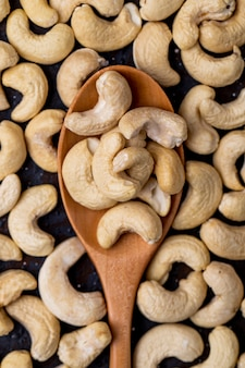 Top view of a wooden spoon with cashew on black background