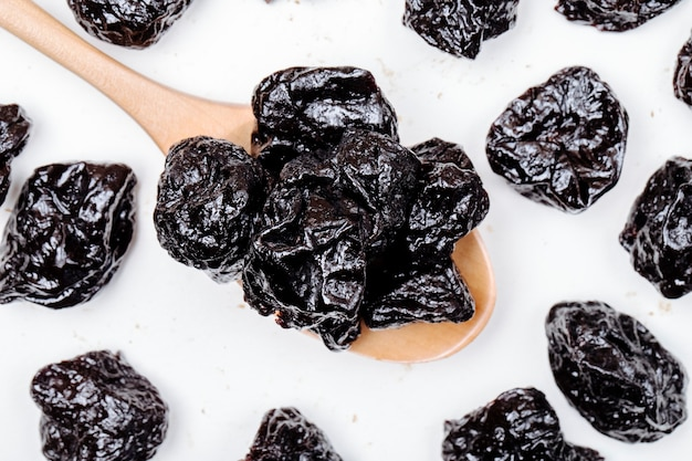 Top view of a wooden spoon with dried plums prunes on white background