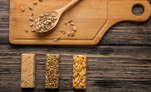 Top view of a wooden spoon with seeds and honey bars with peanuts sesame and sunflower seeds on a wooden board on rustic