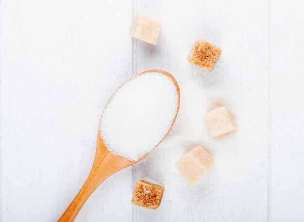 Top view of a wooden spoon with white sugar and lump sugar on white background