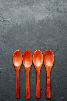 Top view wooden spoons on dark surface with copy place
