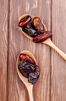 Top view of wooden spoons with dried dates on wooden background