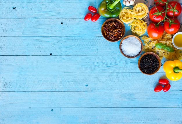 Top view of a wooden table full of italian pasta ingradients like peppers, tomatoes, olive oil, basi