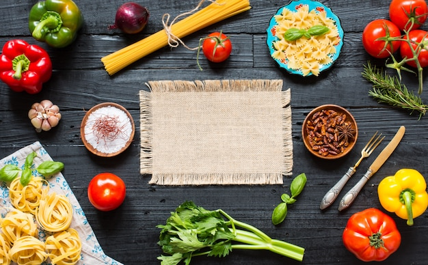 Top view of a wooden table full of italian pasta ingradients like peppers, tomatoes, olive oil, basil