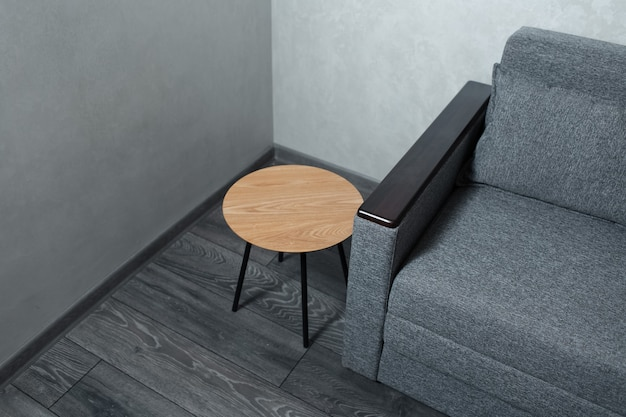 Top view of wooden table and sofa on grey laminate floor.