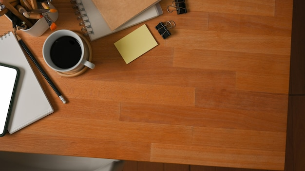 Top view of wooden table with coffee cup, notebooks, stationery and copy space in home office room