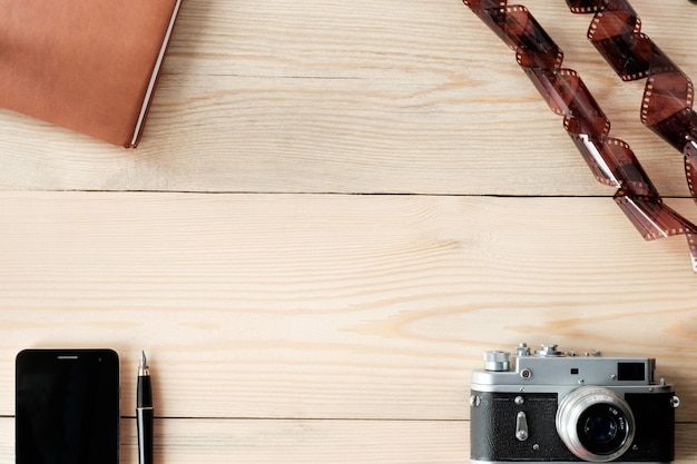 Top view of wooden table with phone; stylus pen, diary, vintage camera and film