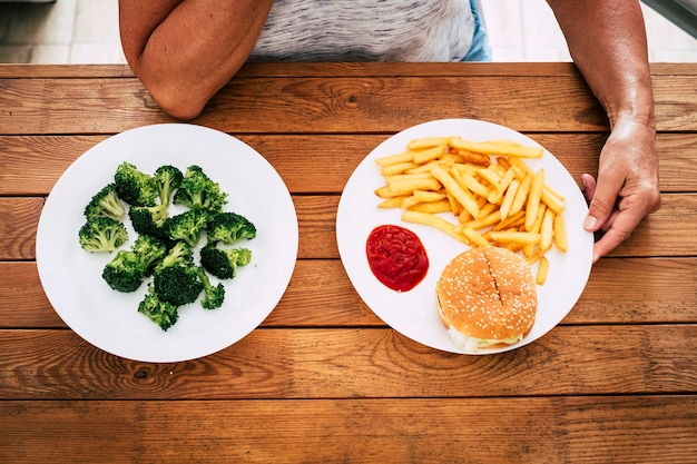 Top view of a wooden table with two plates with haburger and crisps or vegetables like broccoli - choosing healthy of unhealthy lifestyle