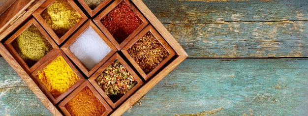Top view of wooden tray filled with full of ground colorful spices