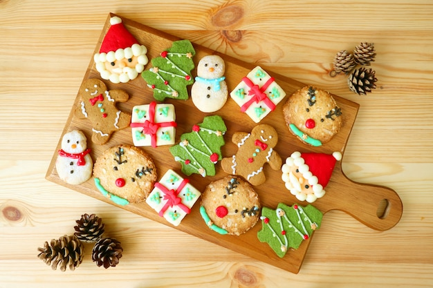 Top view of a wooden tray full of tasty christmas cookies decorated with dry pine cones