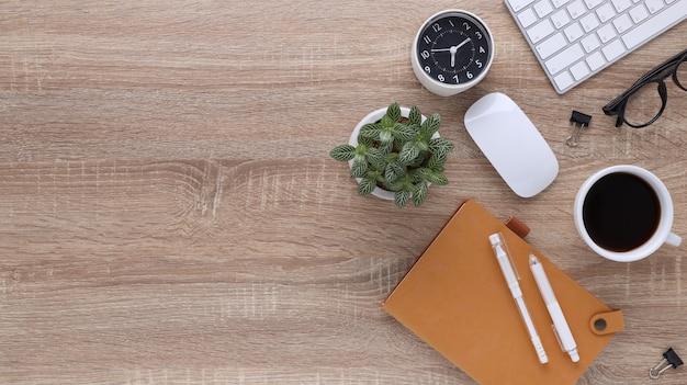 컴퓨터와 사무용품이 있는 탑 뷰 목재 작업 공간 사무실 책상. 빈 노트북, 키보드, 펜, 스마트폰, 커피 컵이 있는 평평한 작업 테이블. 광고 콘텐츠를 위한 공간을 복사합니다.