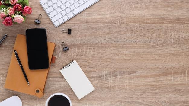 Деревянный офисный стол рабочего места взгляд сверху с компьютером и канцелярскими принадлежностями. плоский рабочий стол с пустой записной книжкой, клавиатурой, ручкой, смартфоном и кофейной чашкой. скопируйте место для вашего рекламного контента.