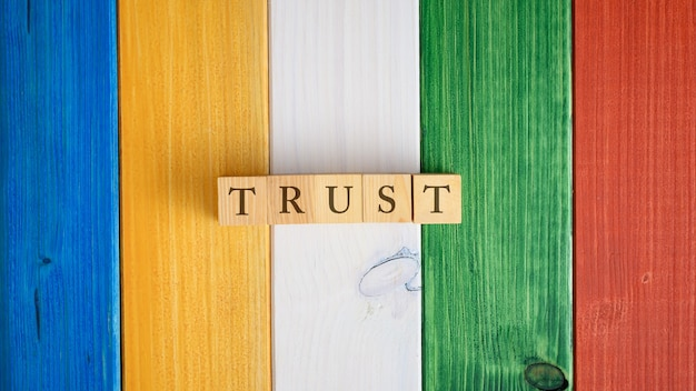 Top view of the word trust spelled on wooden cubes on colorful background of wooden planks.