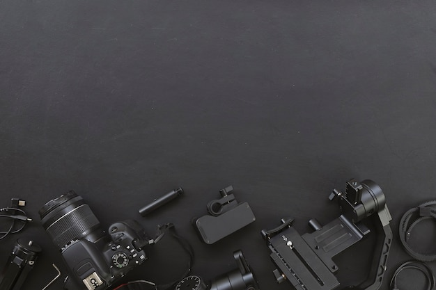 Top view of work space photographer with digital camera and accessory on black background