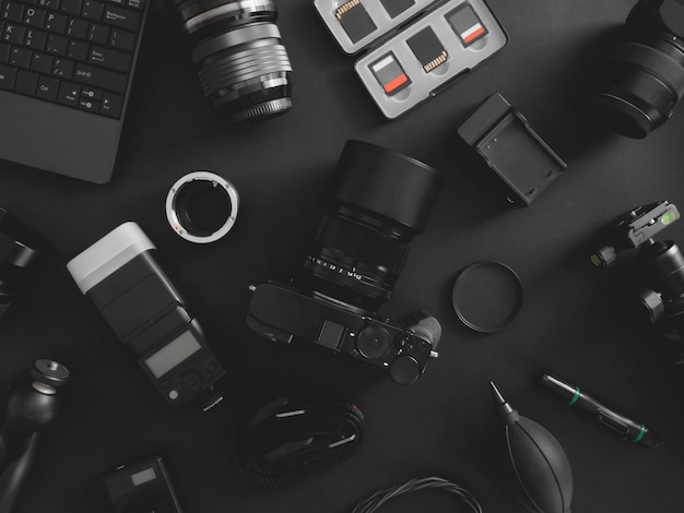 Top view of work space photographer with digital camera, flash, cleaning kit, memory card, tripod and camera accessory on black table background