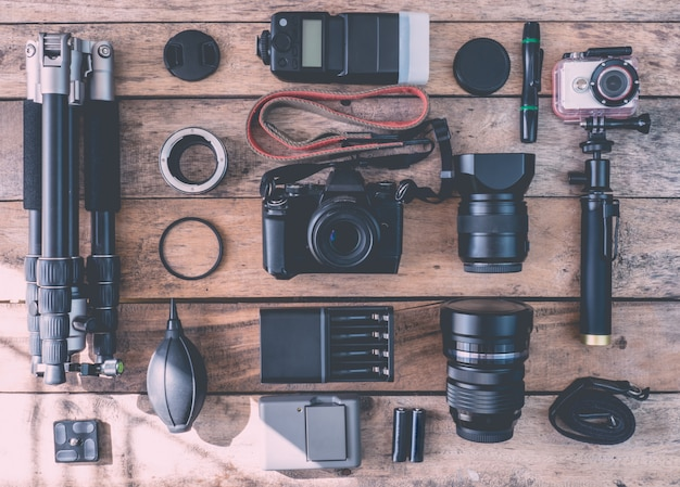 Top view of work space photographer with digital camera, flash, cleaning kit, memory card, tripod and camera accessory on wooden table background