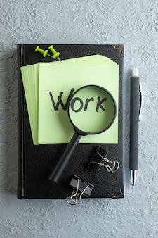 上面図の作品は、白い背景の上のメモ帳と拡大鏡で緑のステッカーにメモを書いた大学の色の仕事学校のオフィスのビジネスコピーブック