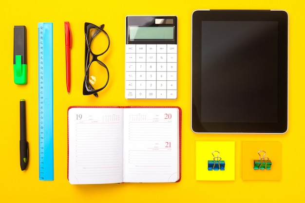 Top view of working space table with tablet, notebook and pen isolated on yellow background